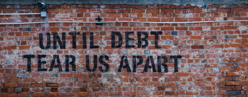 """brick wall with words painted """"until debt tears us apart"""" -financial stress from debt"""