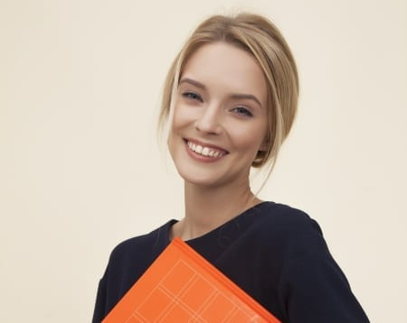 blond hair woman holding an orange folder - how to be confident