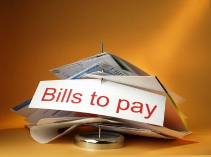 ways to save on utility bills - stack of bills on a desk spindle