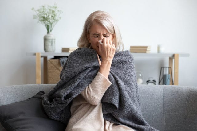 how to boost your immune system - sick woman sitting on couch wrapped in grey blanket