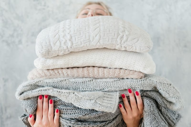woman holding blankets looking for blanket storage ideas